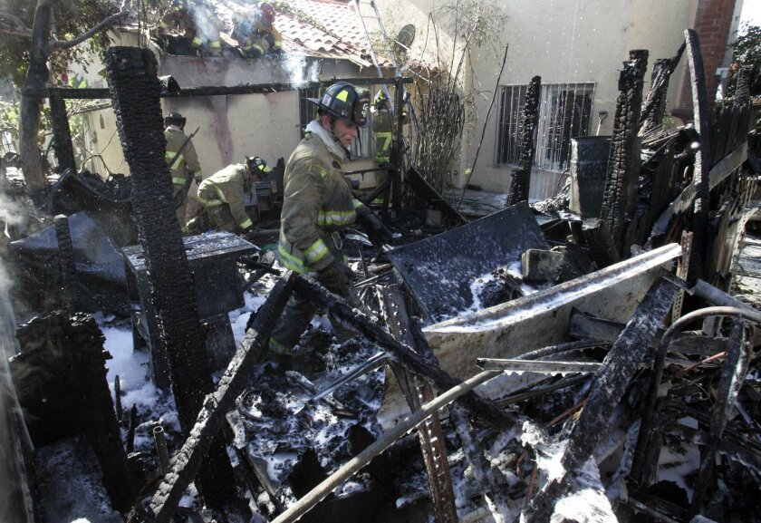 San Diego firefighters Barry Smith removing debris from a burnt building.