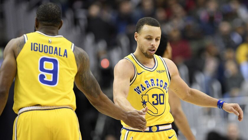 Golden State Warriors guard Stephen Curry (30) and guard Andre Iguodala (9) react during the second half of the team's NBA basketball game against the Washington Wizards.