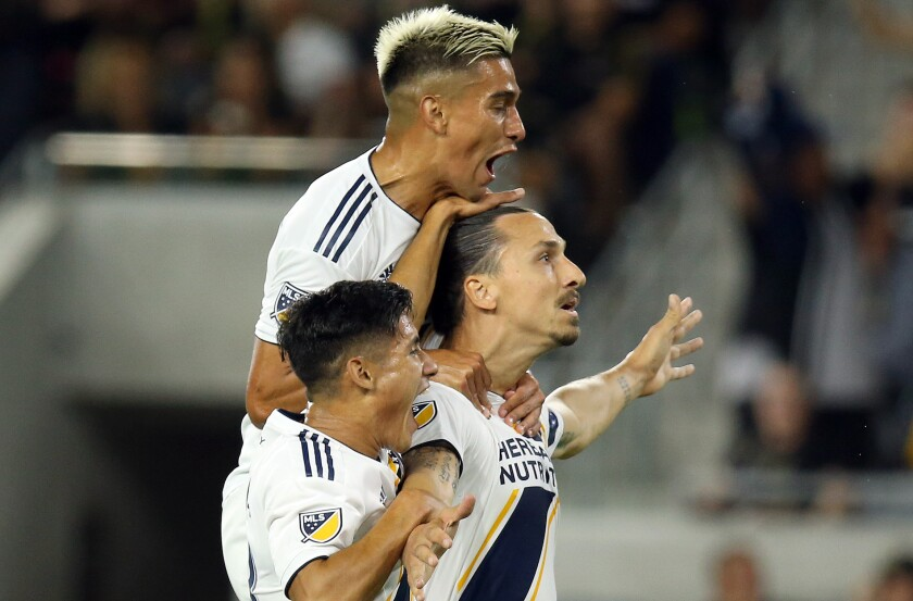 Galaxy forward Zlatan Ibrahimovic (center) celebrates with teammates Favio Alvarez (top) and Uriel Antuna after scoring his second goal against LAFC on Sunday.