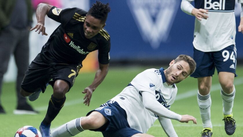 Vancouver Whitecaps midfielder Ion Erice, lower right, fights for control of the ball with Los Angel