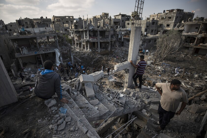 Palestinians inspect their destroyed houses in Gaza.