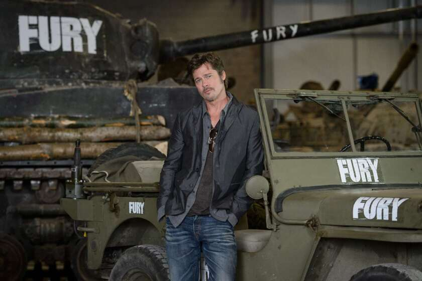 """Brad Pitt poses at a media event to promote his latest film, """"Fury,"""" at the Bovington Tank Museum in Dorset, Britain, on Aug. 28."""