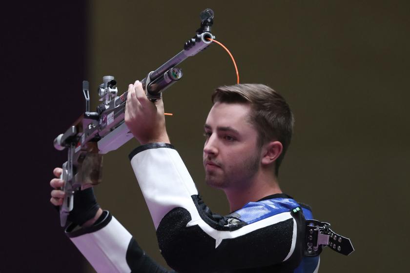 William Shaner del equipo de Estados Unidos levanta su rifle después de ganar el oro.
