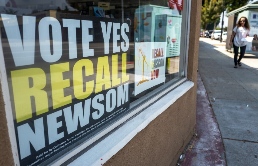 A sign urging people to vote yes on recalling Gov. Gavin Newsom sits in a storefront window in Burbank on Aug. 25.