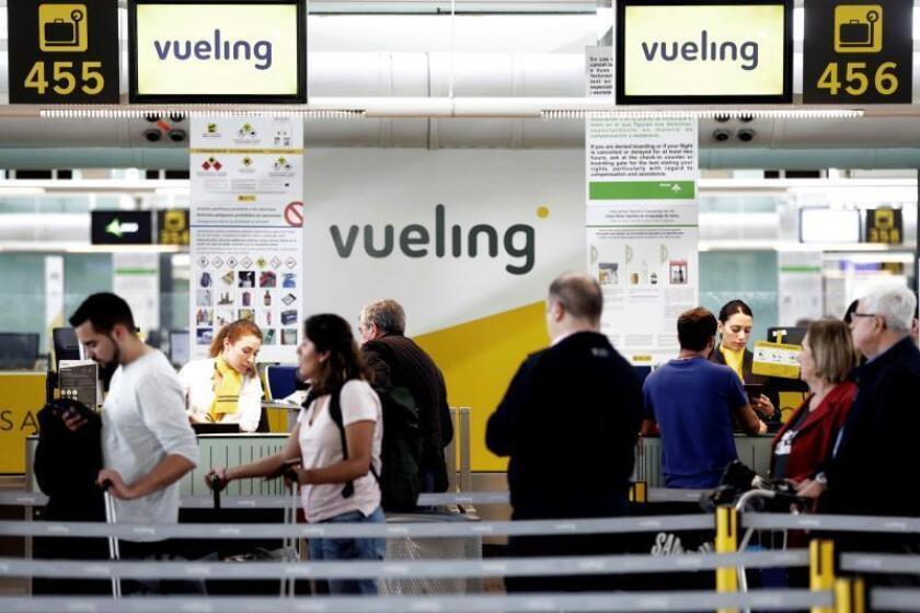 Un grupo de pasajeros ante un mostrador de facturacion de Vueling en el Aeropuerto de Barcelona-El Prat. EFE/Archivo