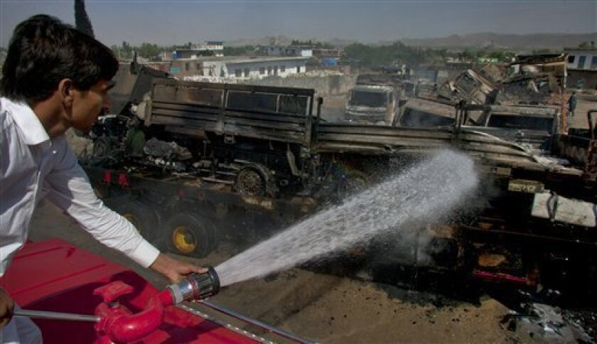 A firefighter sprays water on a burning truck torched by suspected militants in an attack, early Wednesday, June 9, 2010, in Sangjani near Islamabad, Pakistan. Suspected militants attacked trucks carrying military vehicles and goods for foreign forces in Afghanistan close to the Pakistani capital, killing six people and wounding seven others, police and witnesses said. (AP Photo/Anjum Naveed)