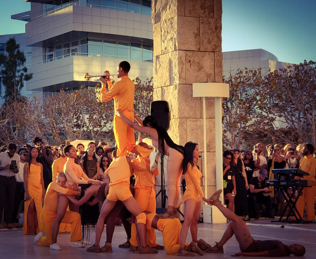 R&B singer Solange, wearing sunglasses toward the left, watches a dance performance at the Getty Center.