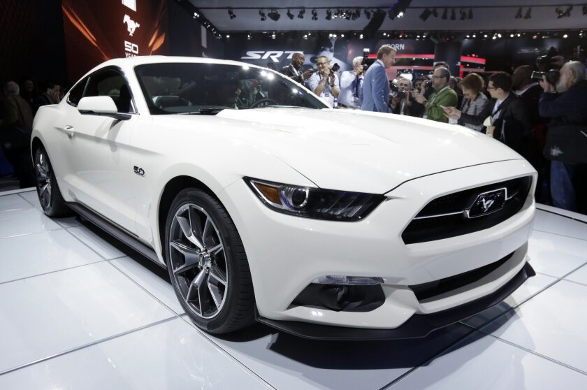 FILE - In this April 16, 2014 file photo, the 2015 Ford Mustang 50 Year Limited Edition is introduced at the 2014 New York International Auto Show at the Javits Convention Center, in New York. For 2015, the now half-century-old Mustang adds a modern, 310-horsepower, turbocharged four cylinder that's fuel efficient and refined even as it delivers more horsepower and torque than the Mustang's V-6. (AP Photo/Richard Drew, File)