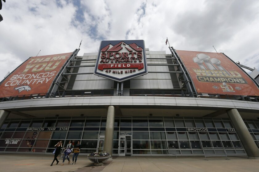 In this Thursday, May 26, 2016, photograph, shoppers leave the team store below the sign for Sports Authority Field at Mile High on the south end of the stadium that is the home of the NFL football team Denver Broncos in Denver. The demise of Sports Authority has reignited a fight in Colorado over
