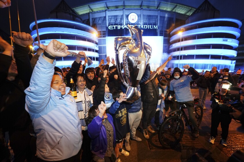 Manchester City supporters celebrate outside the Etihad Stadium in Manchester, England, Tuesday, May 11, 2021 after their team clinched the English Premier League title. City took the title after crosstown rivals Manchester United lost at home to Leicester City. (AP Photo/Jon Super)