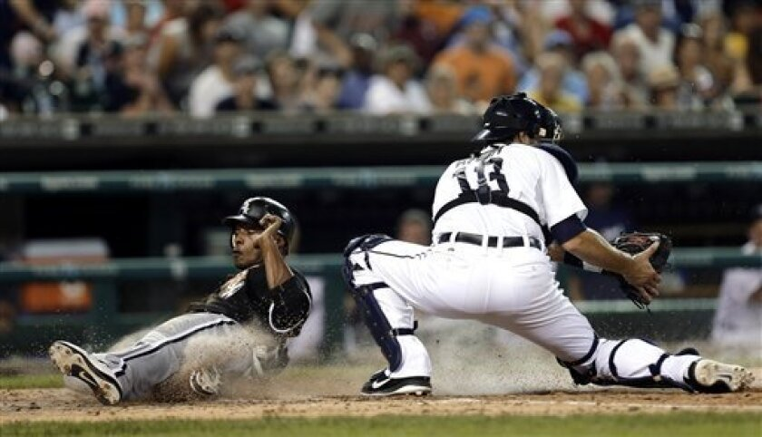 Chicago White Sox's Dewayne Wise (28) slides safely across home plate to score on a Paul Konerko fly ball as Detroit Tigers catcher Alex Avila (13) receives the late throw in the sixth inning of a baseball game in Detroit, Friday, Aug. 31, 2012.  (AP Photo/Paul Sancya)