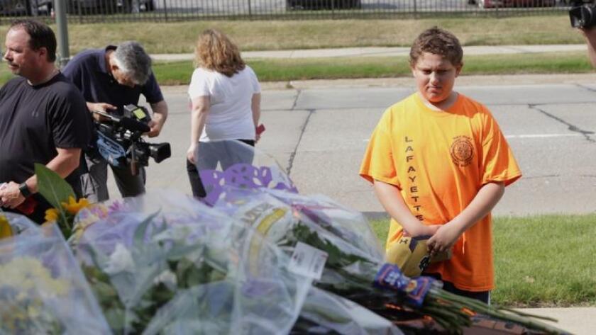 Luciano Antonini, de 12 años, rinde homenaje a dos agentes judiciales, ambos expolicías, asesinados a tiros por un preso en Michigan (Associated Press).