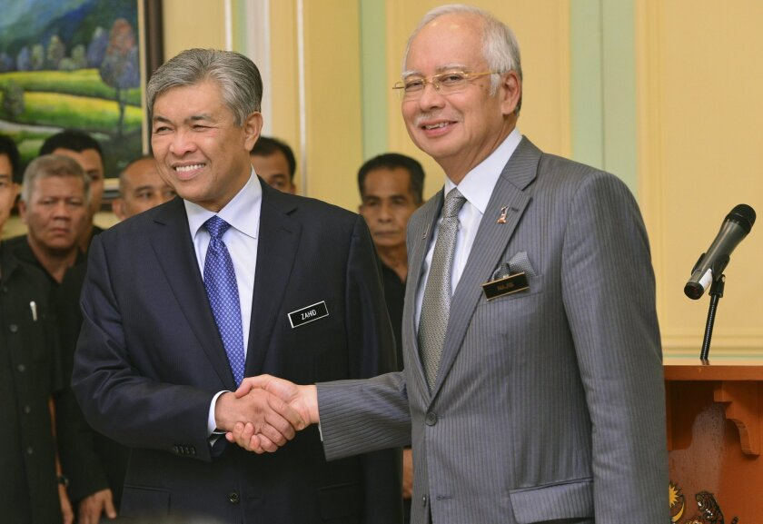 Malaysia's Prime Minister Najib Razak, right, shakes hands with his newly-appointed Deputy Prime Minister Ahmad Zahid Hamidi after addressing a press conference at the prime minister's office in Putrajaya, Malaysia, Tuesday, July, 28, 2015. Najib has axed his deputy in a Cabinet reshuffle and sacked the attorney general, who heads a task force investigating allegations that Najib received some $700 million in government money. (AP Photo)