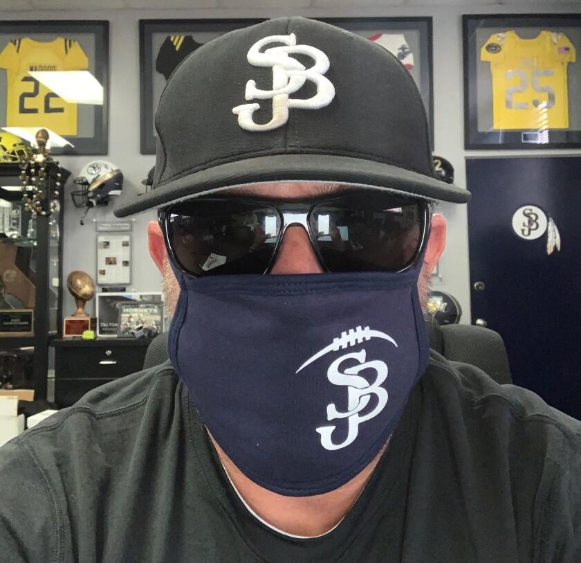 St. John Bosco football coach Jason Negro shows off his specially made mask.