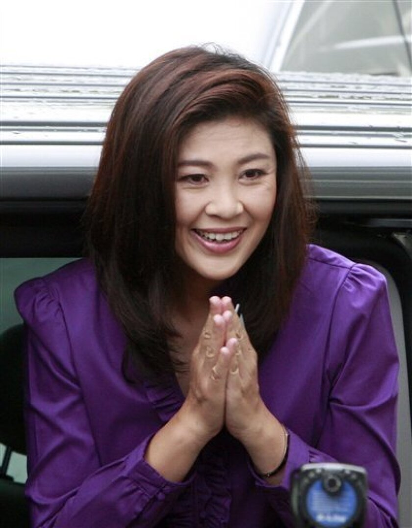 Opposition Pheu Thai party leader Yingluck Shinawatra greets upon her arrival at a polling station to cast her ballot in a general election in Bangkok, Thailand Sunday, July 3, 2011. (AP Photo/Apichart Weerawong)