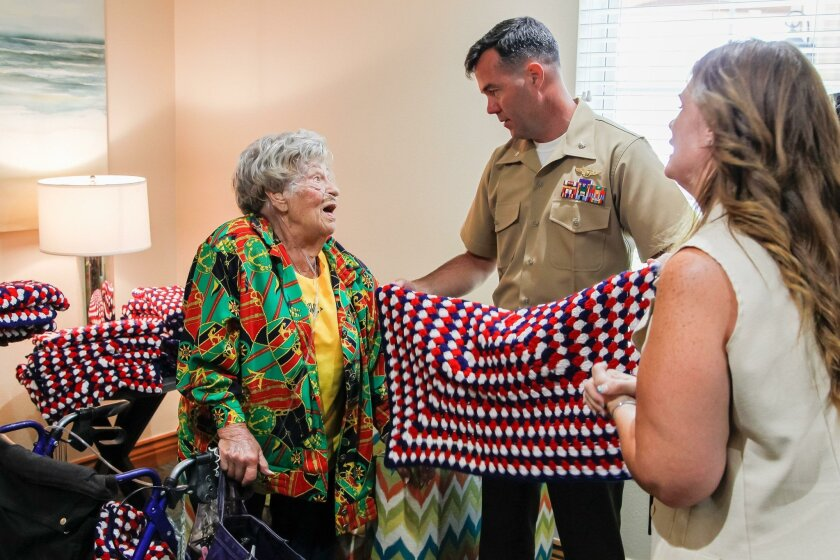 Sylvia Winderbaum, 100 (left), gives a lap robe blanket to Lt. Col. Stephen Mount and Tonjia Berger-Day of the Wounded Warrior Battalion-West.