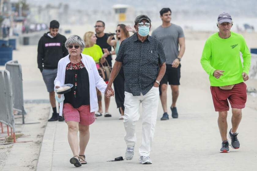 People walk along the boardwalk in Pacific Beach on Wednesday, May 12, 2021.