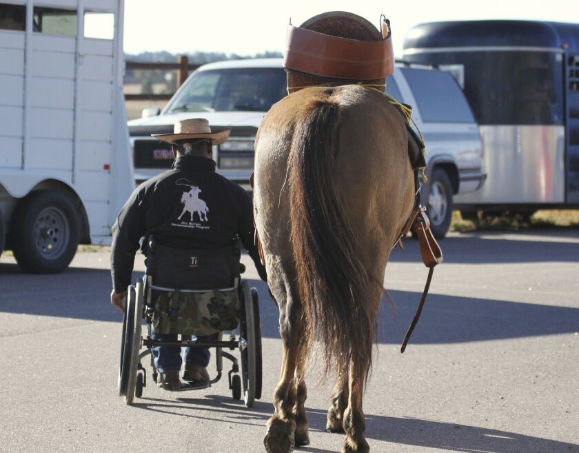 An injured veteran returns from a horse therapy session as part of the Jinx McCain Horsemanship Program, one of the rehabilitative sports programs supported by the Semper Fi Fund. Photo by Julie Bender.