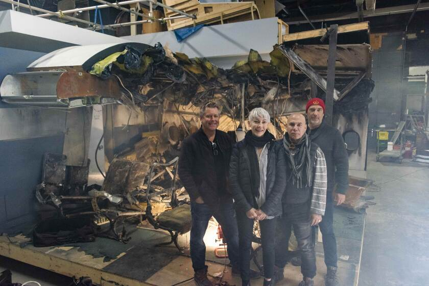 "Director Tim Wolochatiuk, left, line producer Lana Pitkin, production designer Ricardo Barcelo and cinematographer James Griffith stand before a charred cabin set in the ""Air Disasters"" studio in Toronto."