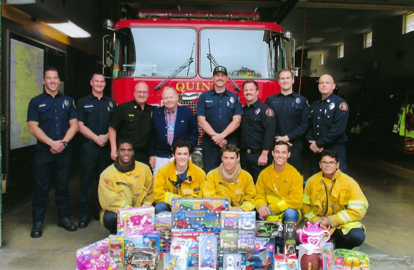 Jim Hughes, fourth from left, Grand Knight representing the La Crescenta-Montrose Knights of Columbus membership, delivers new toys to L.A. County Fire Station #82 in La Canada Flintridge for their Toy.