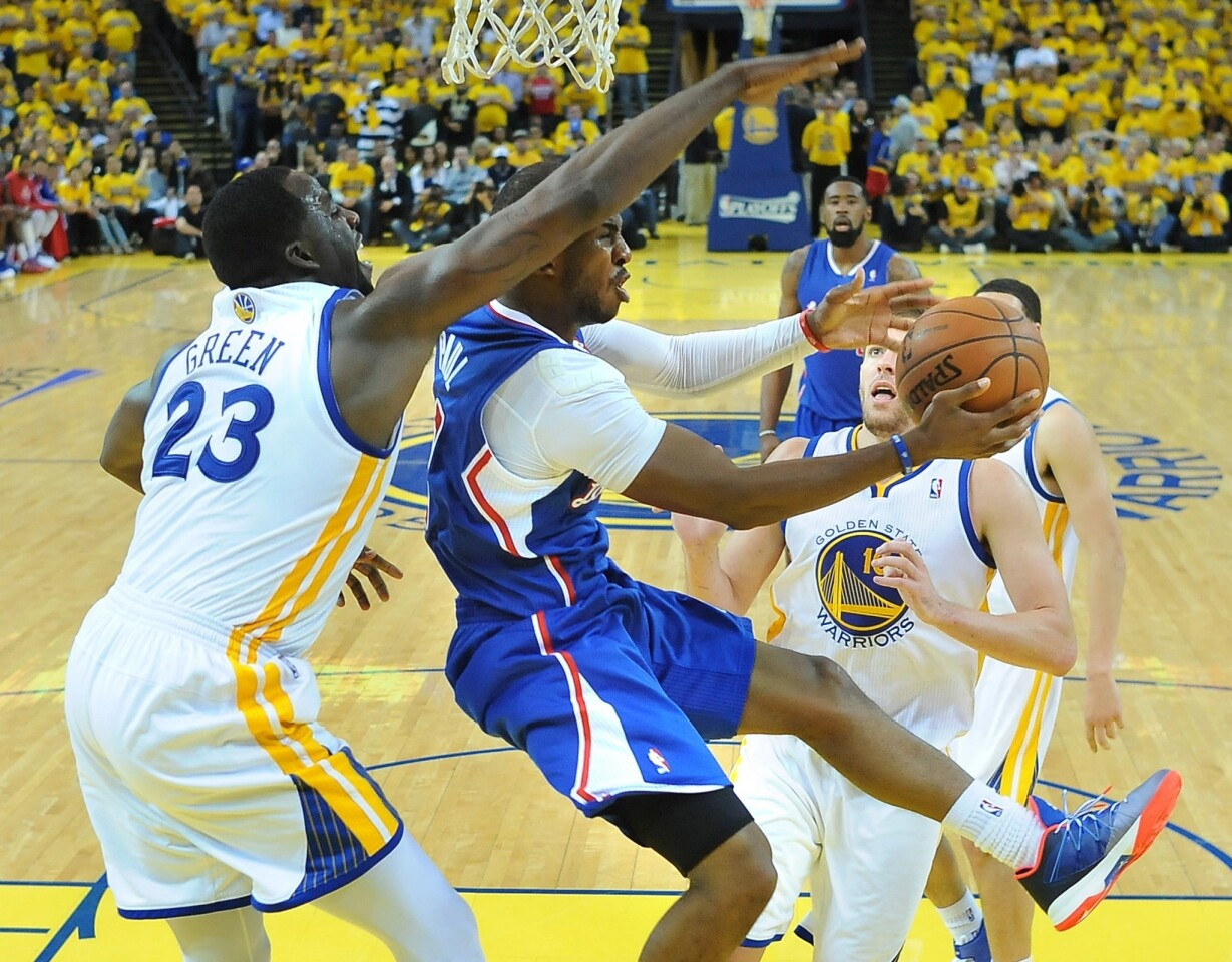 Clippers point guard Chris Paul, who finished with 15 points and 10 assists, attempts a reverse layup against Warriors power forward Draymond Green in Game 3 on Thursday night in at Oracle Arena in Oakland.
