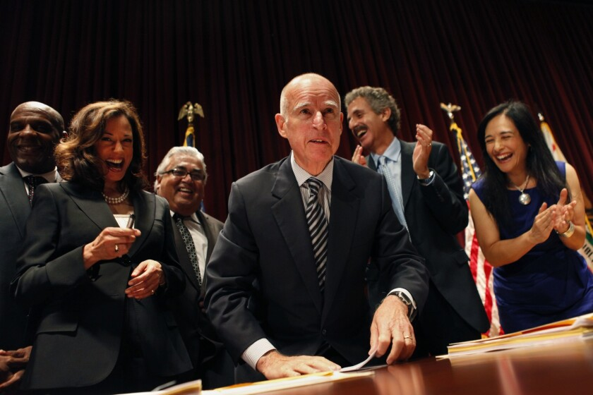 Gov. Jerry Brown, center, flanked by Atty. Gen. Kamala Harris, left, and Maria Cabildo of the East Los Angeles Community Corp., right, signs the Homeowner Bill of Rights foreclosure legislation at the Ronald Reagan State Building in July 2012 in Los Angeles.