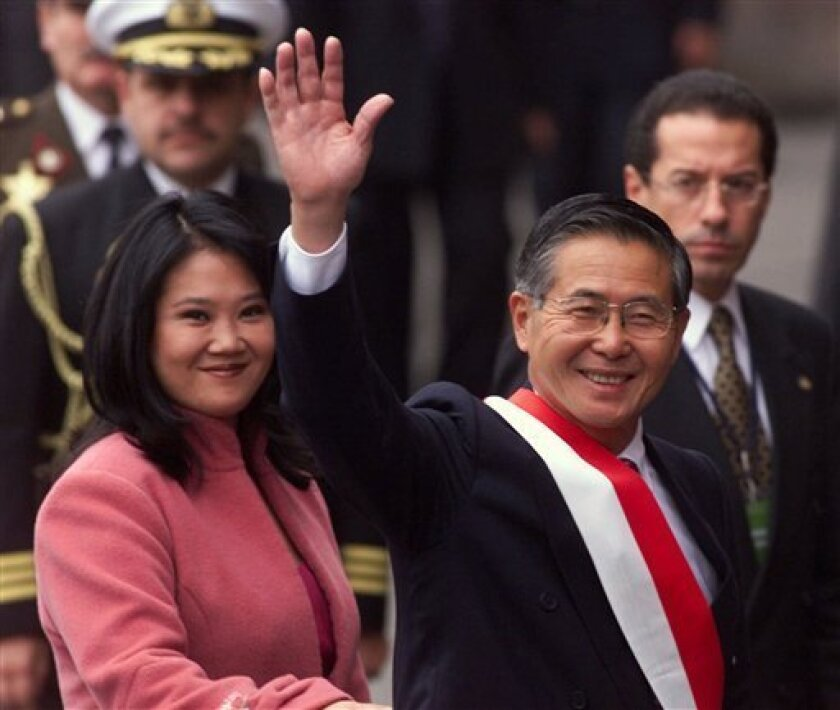 FILE - In this July 28, 2000 file photo, Peru's President Alberto Fuijimori waves as he arrives at the cathedral accompanied by his daughter, Keiko, before his inauguration for a third five-year term, in Lima, Peru. When Fujimori's oldest daughter, Keiko, launched her presidential candidacy two years ago, her stated aim was to free her father, who is serving 25 years for authorizing death squad killings and looting the treasury during his 1990-2000 rule. Now that Keiko has a strong chance to become Peru's first female leader, it is her father's legacy that is casting a shadow over her candidacy. (AP Photo/Ricardo Mazalan, File)