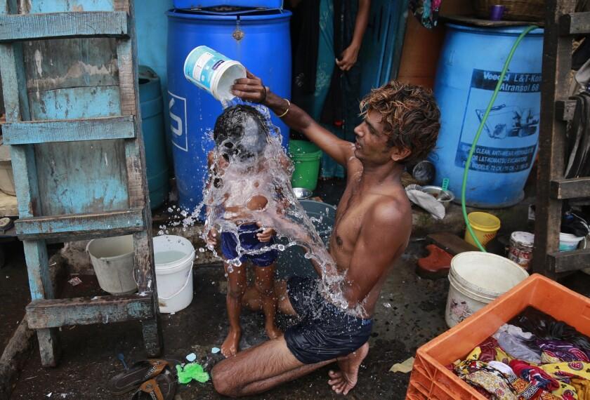 ARCHIVO - En esta fotografía de archivo del 23 de mayo de 2016, un hombre baña a su hijo una calurosa tarde en Mumbai, India. La Tierra hirvió en su 13vo mes consecutivo en romper el récord de mes más caluroso en mayo, aunque no con temperaturas tan abrasadoras como en meses previos, según científicos del gobierno. (AP Foto/Rafiq Maqbool, Archivo)