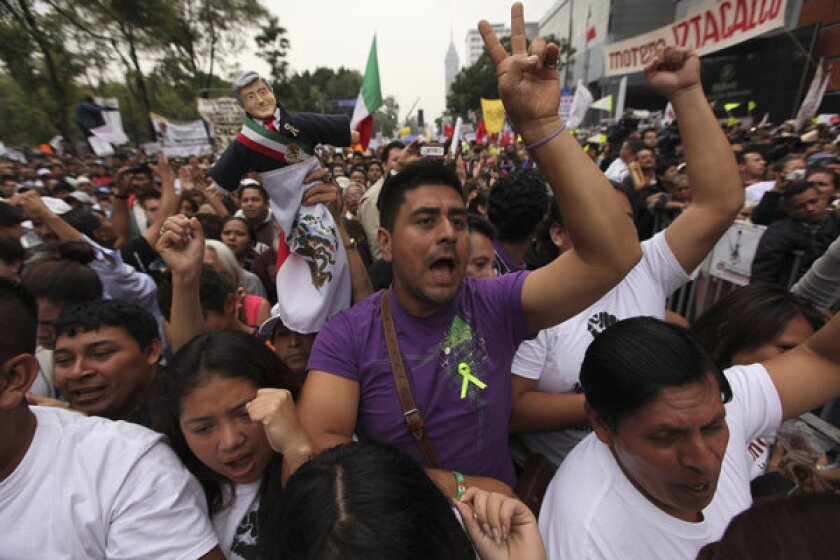 Supporters of former presidential candidate Andres Manuel Lopez Obrador cheer as they listen to him Sunday during a demonstration in Mexico City against the government's proposed energy reforms that would allow private companies to explore the country's oil and gas reserves.