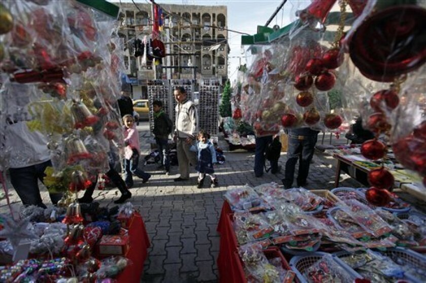 People walk past a street vendor selling Christmas decorations in downtown Baghdad, Iraq, Wednesday, Dec. 22, 2010. Church officials in Iraq say they have canceled some Christmas festivities in two northern cities over fears of insurgent attacks. (AP Photo/Hadi Mizban)