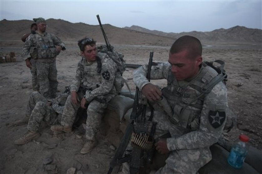 In this May 21, 2010 photo, from left, U.S. Army Sgt. Jacob Zimmerman, of Osh Kosh, Wis., Spc. Timmy Hartbeck of Manchester, Iowa, and Spc. Kevin O'Connor, of Hingam, Mass. wait for darkness to set in before heading out to set up an ambush for the Taliban, in the Shah Wali Kot district of Afghanistan's Kandahar province. Zimmerman, Hartbeck and O'Connor, are all member of 2nd Platoon, Charlie Company which suffered 12 casualties, including one Afghan interpreter, during its 12-month deployment with 1st Battalion, 17th Infantry Regiment of the 5th Stryker Brigade, 2nd Infantry Division. Twenty-two men in the U.S. Army's 1st Battalion, 17th Infantry Regiment of 800 died in a yearlong Afghan tour ending this summer. Most were killed last year in the Arghandab, a gateway to the southern city of Kandahar. About 70 were injured, all but two in bomb blasts. (AP Photo/Julie Jacobson)