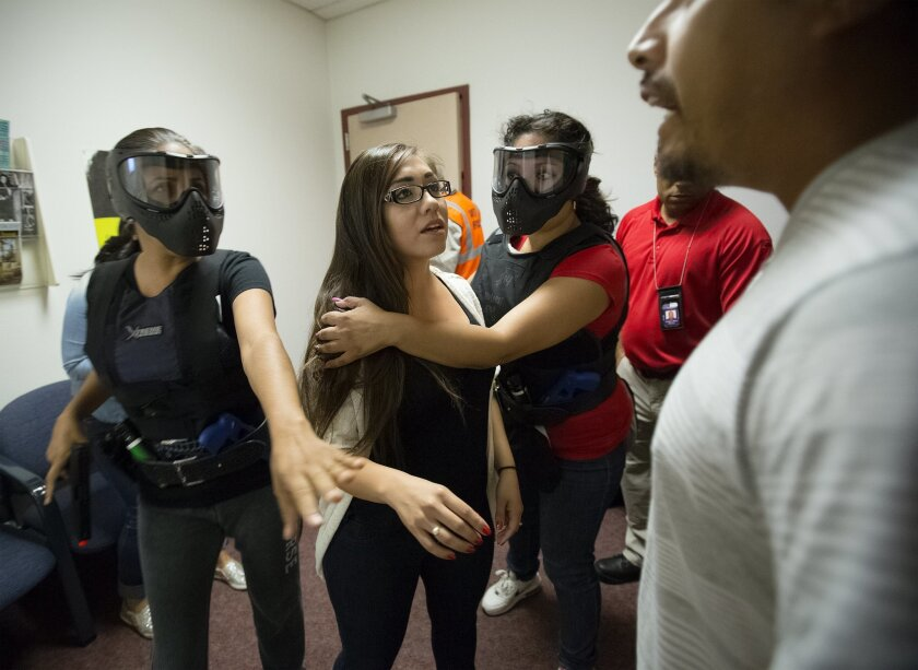 Portraying police officers, Luisa McCarthy (left) with La Vista Memorial Park and Vianey Rivera (3rd from left) from National City, Neighborhood Services Division respond to a scenario setup as a domestic violence and portrayed by role players, Elyana (cq) Delgado (girl in center) and NCPD officer Sal Gil (far right).