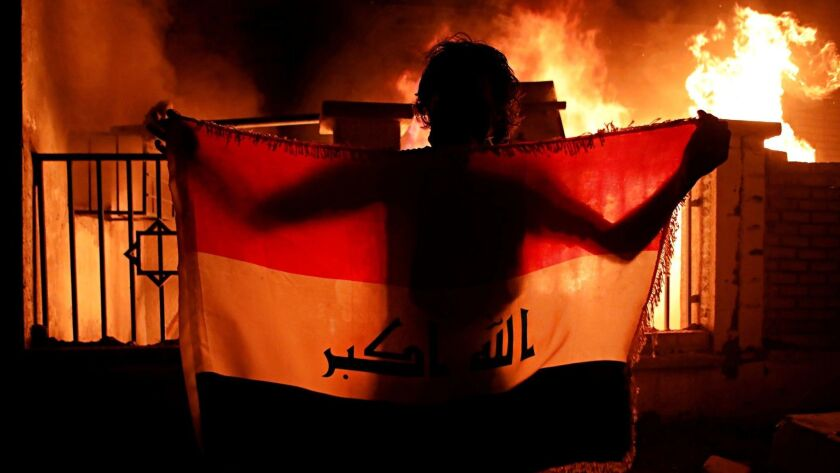 A man holds a national flag while protesters burn the municipal complex during protests demanding be
