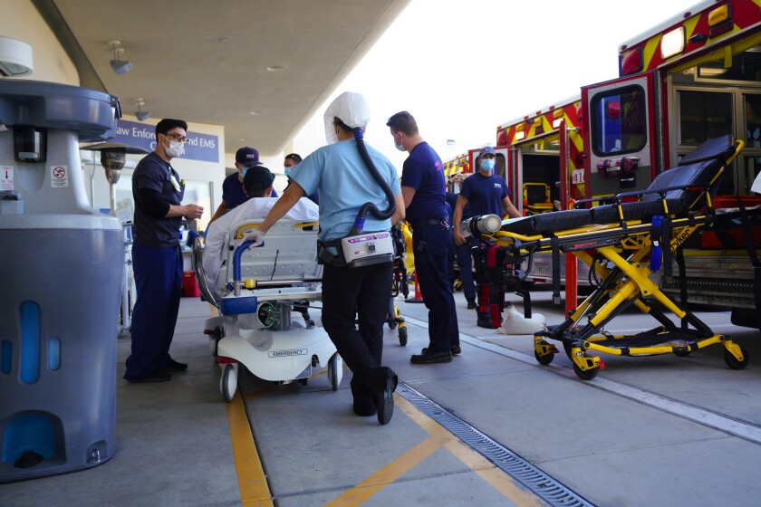 A patient on a stretcher is wheeled from an ambulance into a hospital