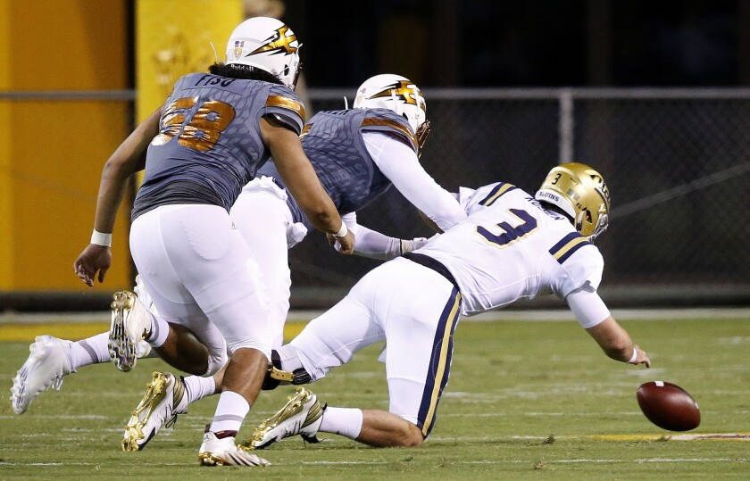 UCLA quarterback Josh Rosen (3) fumbles the ball as Arizona State defensive lineman JoJo Wicker, middle, and Salamo Fiso (58) move in to make a recovery during the first half.