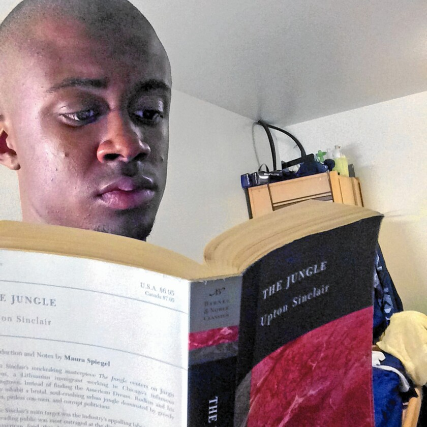 """UC Irvine student Jordan Roberson reads """"The Jungle,"""" by Upton Sinclair. Roberson took second place for a reading contest in February for Black and Latino Men Read."""