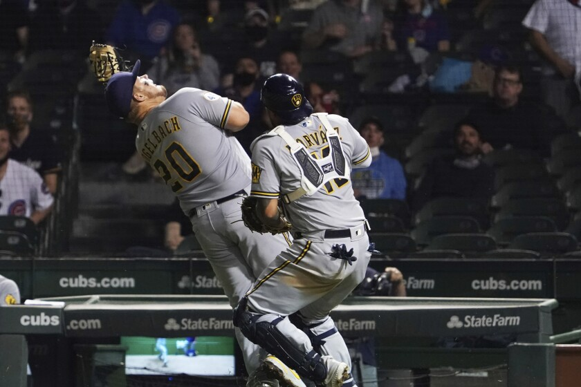 Milwaukee Brewers first baseman Daniel Vogelbach (20) catches a foul ball hit by Chicago Cubs' Jason Heyward as catcher Omar Narvaez (10) also chases it during the fifth inning of a baseball game Tuesday, April 6, 2021, in Chicago. (AP Photo/David Banks)