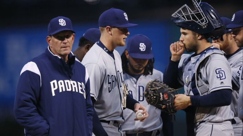 Padres pitching coach Darren Balsley, left, heads back to the dugout after conferring with starting pitcher Eric Lauer in the first inning Tuesday night at Coors Field.