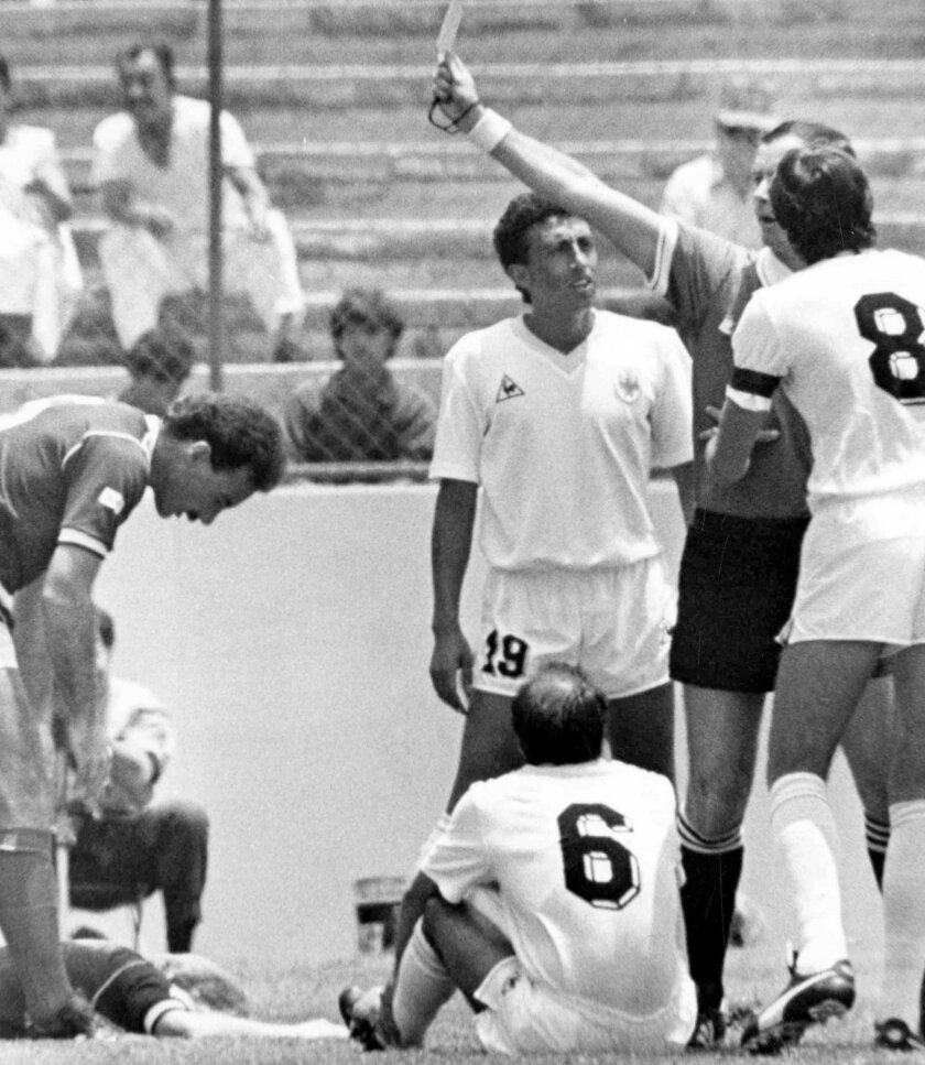 FILE - In this June 13, 1986 file photo, French referee Joel Quiniou, rear right, shows a red card to Uruguayan player Jose Batista, seated centre, for a bad tackle on Scotland's Gordon Strachan, on the pitch left, within the first minute of the start of the World Cup soccer match between Scotland and Uruguay in Mexico City, Mexico. Uruguayan players Jorge Barrios, right and Venacio Ramos, third right, appeal against the sending off. The game ended in a 0-0 draw. On this day: Uruguay's Bastista gets the fastest red card in World Cup history. (AP Photo/Bob Dear, File)