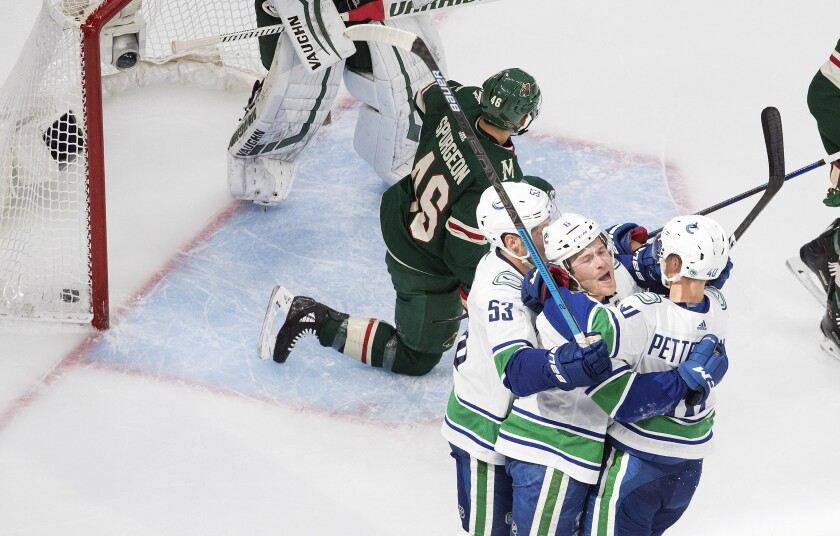 Minnesota Wild's Jared Spurgeon (46) kneels as Vancouver Canucks' Bo Horvat (53), Brock Boeser (6) and Elias Pettersson (40) celebrate a goal during second-period NHL hockey game action in Edmonton, Alberta, Thursday, Aug. 6, 2020. (Jason Franson/The Canadian Press via AP)