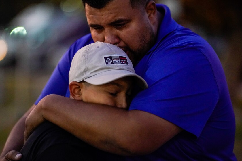 Xavier Martin hugs his son, Sebastian Martinez, who played football with Saugus High School shooting victim Dominic Blackwell