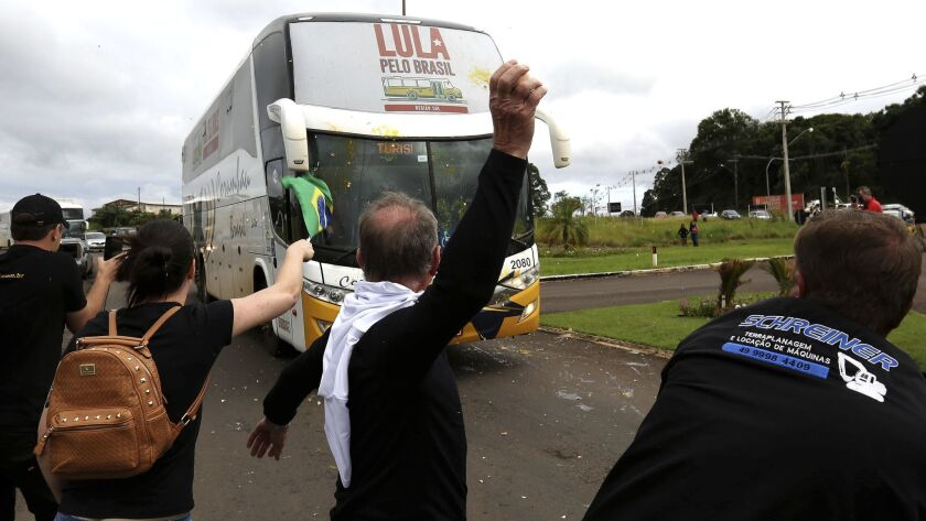 Opponents of Brazil's former President Luiz Inacio Lula da Silva throw eggs at his caravan arriving in Sao Miguel do Oeste in southern Brazil, Sunday, March 25, 2018.