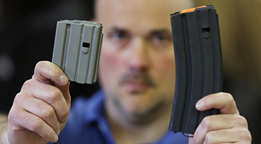 In this April 10, 2013 file photo, Jonathan Scalise, owner of Ammunition Storage Components, holds up a 10-round, left, and a 30-round magazine that his company manufacturers for the AR-15 rifle in New Britain, Conn. Gun rights supporters are suing Connecticut officials over part of a 2013 state gun control law passed after the Sandy Hook school shooting, saying it unconstitutionally bans people from loading more than 10 rounds of ammunition into their firearms. The lawsuit filed in U.S. District Court on Tuesday, March 10, 2020 cites the Second Amendment right to bear arms and the ability of people to better defend themselves with more bullets in their guns. (AP Photo/Charles Krupa, File)