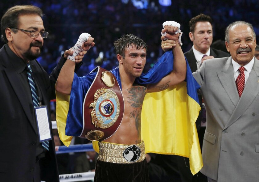 FILE - In this Sunday, Nov. 23, 2014 file photo, Vasyl Lomachenko of Ukraine celebrates after defeating Chonlatarn Piriyapinyo of Thailand during their WBO world featherweight boxing title match at the Venetian Macao in Macau. Vasyl Lomachenko is a ferocious puncher and a two-time Olympic gold meda