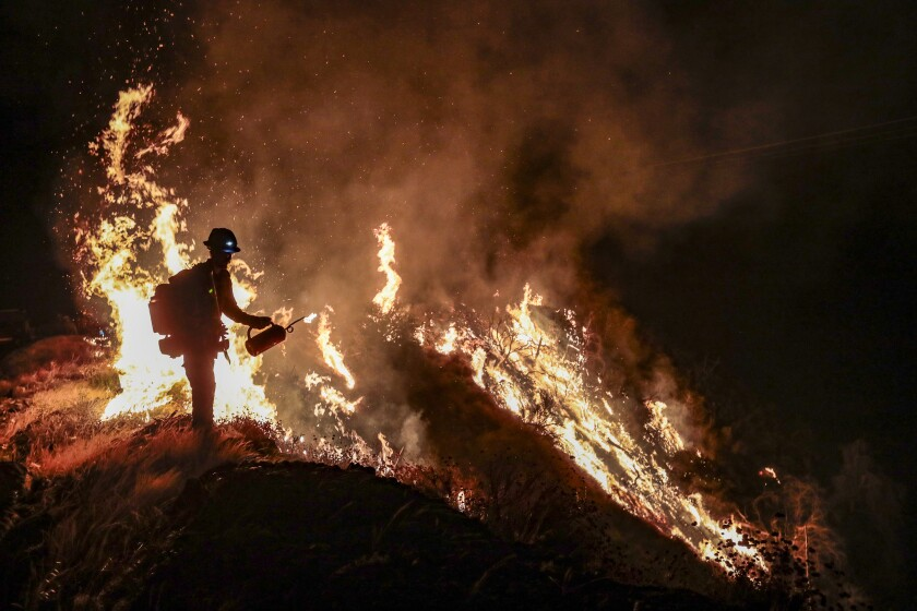 A firefighter at night next to flames on a hillside