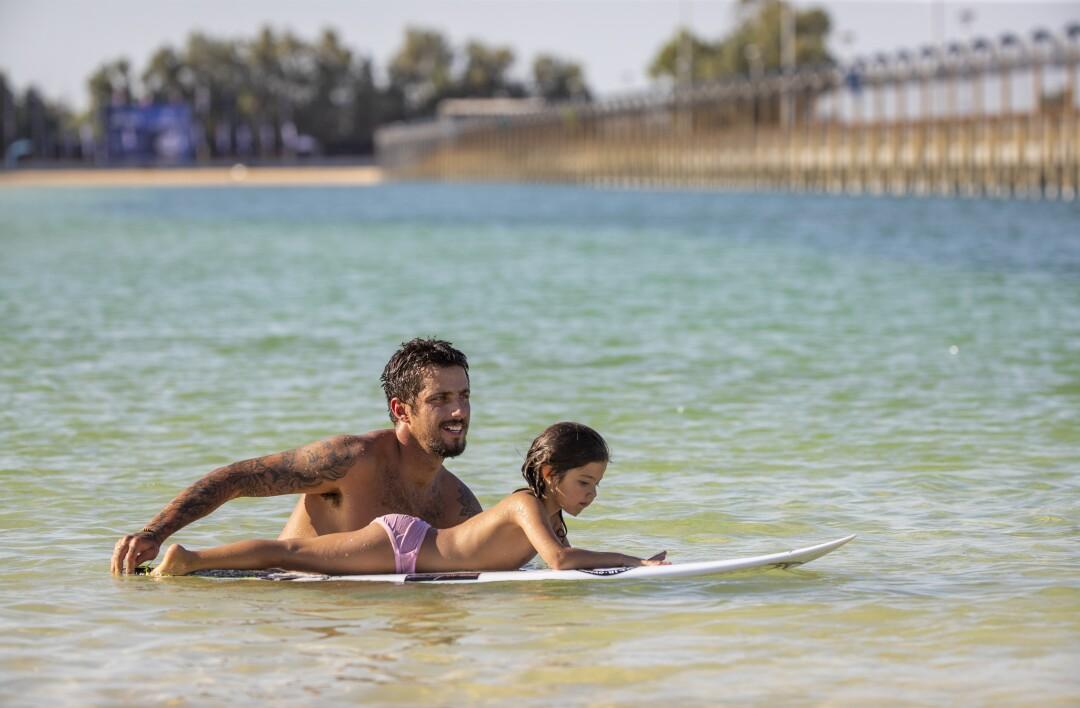 Filipe Toledo pushes his child around on his surfboard