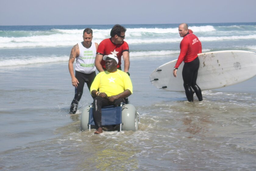 Anthony Evans, with some help, gets ready to surf on Tuesday.