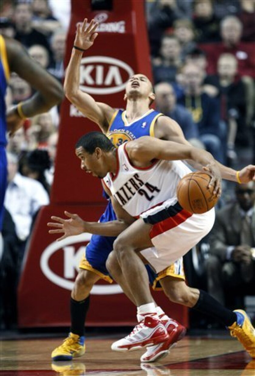 Portland Trail Blazers' Andre Miller (24) drives as Golden State Warriors' Stephen Curry falls back in the first quarter during an NBA basketball game Tuesday, April 5, 2011, in Portland, Ore.(AP Photo/Rick Bowmer)