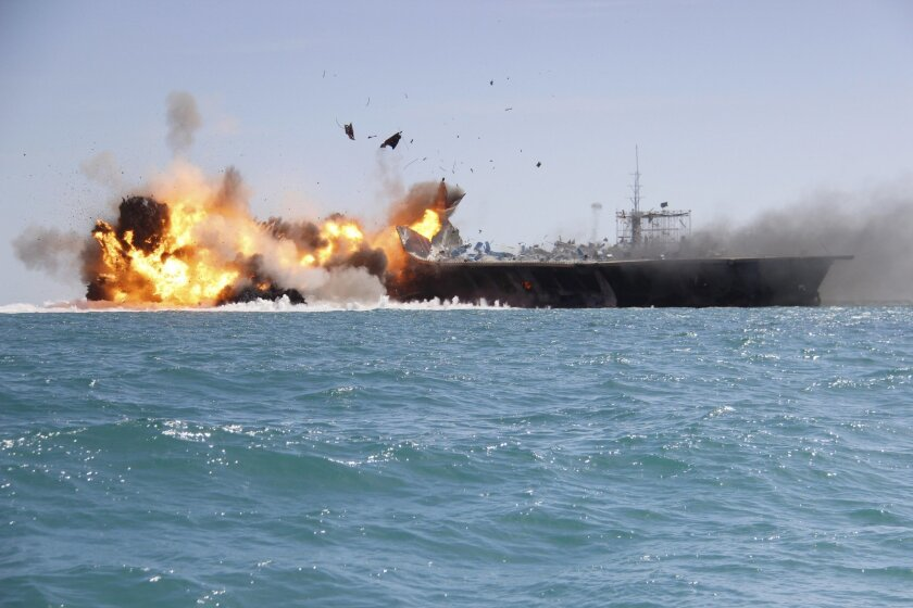 """In this picture released by the Iranian Tasnim news agency on Wednesday, Feb. 25, 2015, a replica of a U.S. aircraft carrier is exploded by the Revolutionary Guard's speedboats during large-scale naval drills near the entrance of the Persian Gulf, Iran. The drill, named Great Prophet 9, was the first to involve a replica of a U.S. carrier. Cmdr. Kevin Stephens, the spokesman for the U.S. Navy's 5th Fleet in Bahrain, said they were monitoring the drills, but downplayed the simulated attack on the carrier, saying the U.S. military was """"not concerned about this exercise.""""(AP Photo/Tasnim News)"""