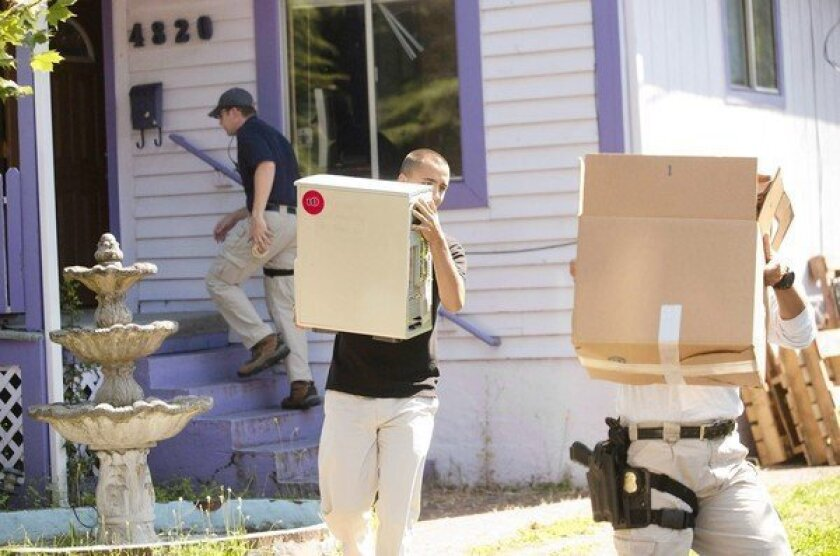 Law enforcement personnel carry out evidence gathered from a home in Portland, Ore. An investigation of anarchists in the Pacific Northwest has led to subpoenas of activists in Seattle, Olympia and Portland.